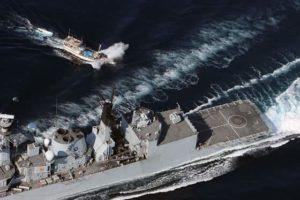 Open sea. Warship intercepts pirate skiff at full speed.