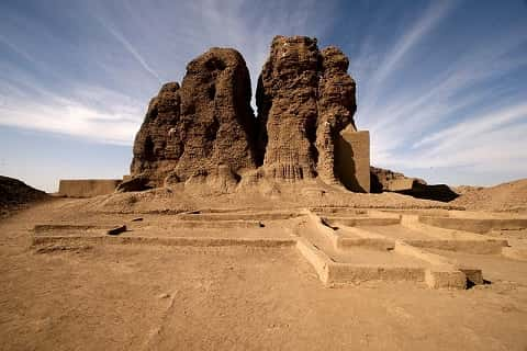 The desert. The ruins of a tower emerge from the sand.