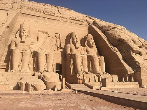 Massive rock temples with colossal sculptures in front.