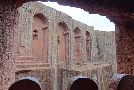 Reddish building carved in rock.
